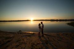 Couples dans le lever de soleil sur la plage Photos stock