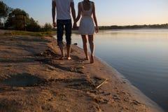Couples dans le lever de soleil sur la plage Photographie stock