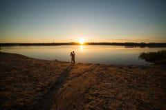 Couples dans le lever de soleil sur la plage Images libres de droits