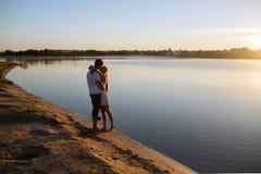 Couples dans le lever de soleil sur la plage Photo libre de droits