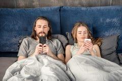 Couples dans le lit avec des smartphones Photographie stock libre de droits