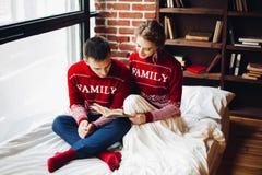 Couples dans le livre rouge de lecture de chandails dans le lit ensemble photos stock