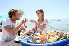 Couples dans le restaurant de fruits de mer faisant le pain grillé Images libres de droits