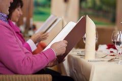 Couples dans le restaurant lisant le menu Photo libre de droits