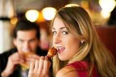 Couples dans le restaurant mangeant des aliments de préparation rapide Photo libre de droits