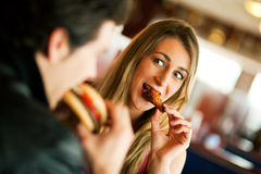 Couples dans le restaurant mangeant des aliments de préparation rapide Image stock