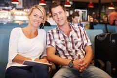 Couples dans le salon de départ d'aéroport attendant pour partir en vacances Image stock
