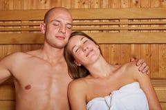 Couples dans le sauna avec des yeux fermés Photographie stock libre de droits