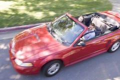 Couples dans le sourire convertible de véhicule image libre de droits