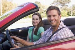 Couples dans le sourire convertible de véhicule photo stock