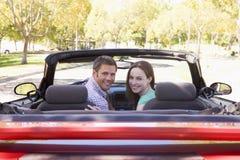 Couples dans le sourire convertible de véhicule Photos stock