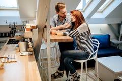 Couples dans le sourire parlant d'amour à la maison Photographie stock