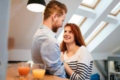 Couples dans le sourire parlant d'amour à la maison Photos stock