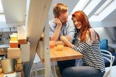 Couples dans le sourire parlant d'amour à la maison Images stock