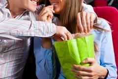 Couples dans le théâtre de cinéma avec le maïs éclaté Images stock