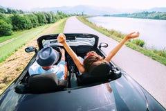 Couples dans le tour d'amour en voiture de cabriolet Photographie stock