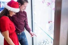 Couples dans le vêtement de Noël regardant l'affichage de montre-bracelet Images libres de droits