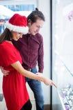 Couples dans le vêtement de Noël regardant l'affichage de montre-bracelet Images stock