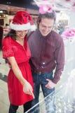 Couples dans le vêtement de Noël regardant l'affichage de montre-bracelet Photographie stock