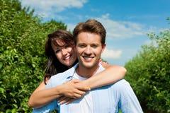 Couples dans le verger de fruit après été Images libres de droits