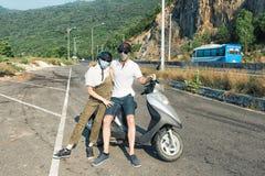 Couples dans les casques et les masques protecteurs asiatiques Photo stock