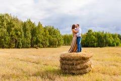 Couples dans les jeunes d'amour embrassant sur la meule de foin Photos libres de droits