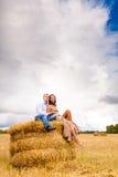 Couples dans les jeunes d'amour se reposant sur la meule de foin Images stock