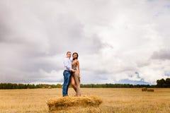 Couples dans les jeunes d'amour se reposant sur la meule de foin Photographie stock libre de droits