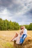Couples dans les jeunes d'amour se reposant sur la meule de foin Photos stock