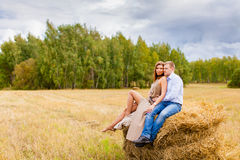Couples dans les jeunes d'amour se reposant sur la meule de foin Photos libres de droits