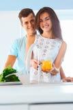 Couples dans les légumes de lavage d'amour dans la cuisine Photos stock
