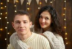 Couples dans les lumières et la décoration de Noël, habillées dans la fille blanche et jeune et l'homme, arbre de sapin sur le fo Images stock
