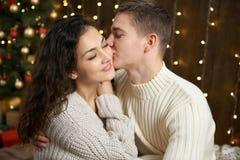 Couples dans les lumières et la décoration de Noël, habillées dans la fille blanche et jeune et l'homme, arbre de sapin sur le fo Image stock