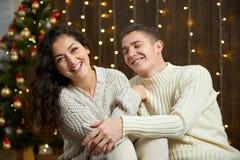 Couples dans les lumières et la décoration de Noël, habillées dans la fille blanche et jeune et l'homme, arbre de sapin sur le fo Images libres de droits