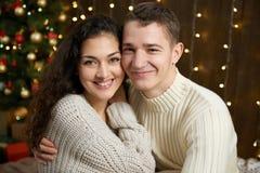 Couples dans les lumières et la décoration de Noël, habillées dans la fille blanche et jeune et l'homme, arbre de sapin sur le fo Photo stock