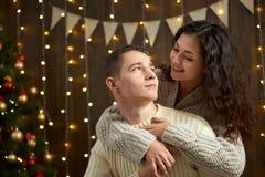 Couples dans les lumières et la décoration de Noël, habillées dans la fille blanche et jeune et l'homme, arbre de sapin sur le fo Photographie stock libre de droits