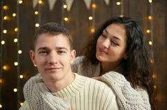 Couples dans les lumières et la décoration de Noël, habillées dans la fille blanche et jeune et l'homme, arbre de sapin sur le fo Image libre de droits