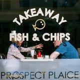 Couples dans les poissons et le Chip Shop, en Devon, l'Angleterre Photos libres de droits