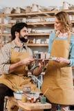 couples dans les tabliers avec des peintures images stock