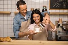 Couples dans les tabliers préparant le café photos libres de droits