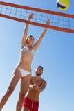 Couples dans les vêtements de bain jouant le volleyball Image stock