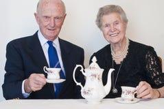 Couples dans leurs années '80 appréciant une cuvette de thé photos libres de droits