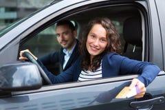 Couples dans sa voiture payant à une cabine de péage photographie stock