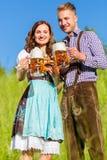 Couples dans Tracht avec de la bière et le bretzel Image libre de droits
