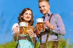 Couples dans Tracht avec de la bière et le bretzel Image stock