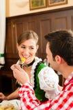 Couples dans Tracht bavarois mangeant dans le restaurant Photo stock