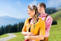 Couples dans Tracht sur le sommet de montagne aux vacances Photo libre de droits