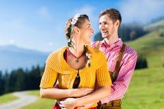 Couples dans Tracht sur le sommet de montagne d'Alpes aux vacances Images libres de droits