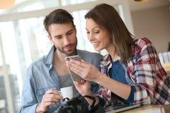 Couples dans un café websurfing sur un smartphone Images libres de droits