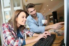 Couples dans un cybercafe websurfing Images libres de droits